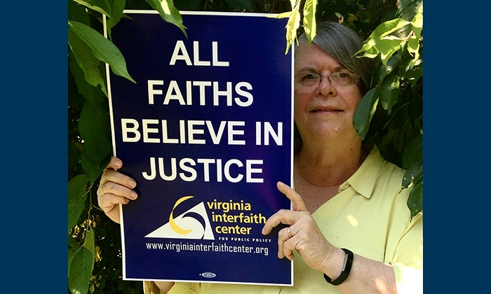 "Stephanie Niedringhaus, a Marymount University alumna, holding a sign that reads, ""All Faiths Believe in Justice."""