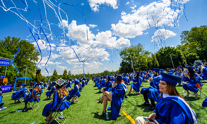 Blue and white streamers fly above graduates during Marymount University's 2021 Commencement Ceremonies