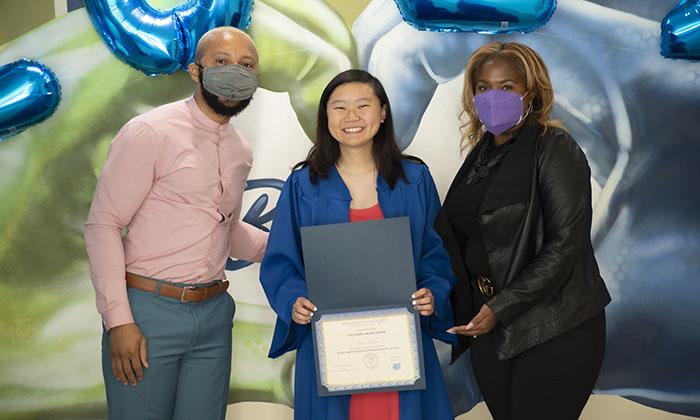 Graduate Anna Moon, center, receives her Cultural Graduation certificate alongside Dean Brooke Berry, right, and Associate Director Tait Brooks, left.