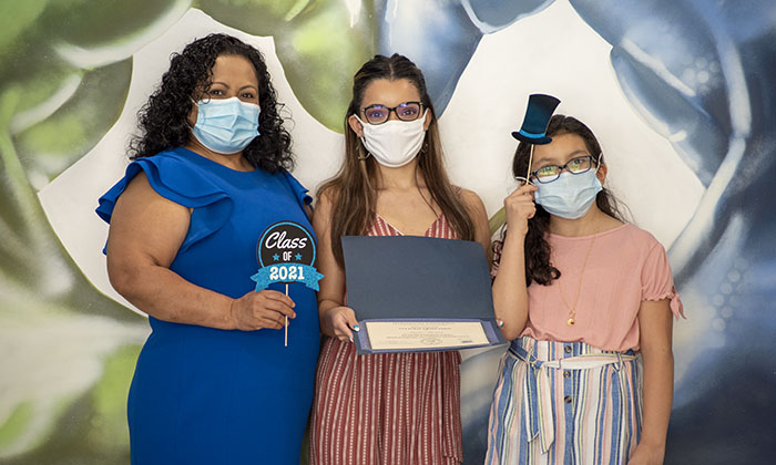 Lisette Benitez, center, celebrates becoming the first college graduate in her family alongside her mother and sister.