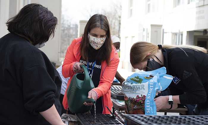 Dr. Agolini, who was selected for a competitive USDA fellowship, waters newly planted herbs with Marymount University students