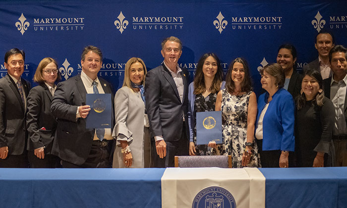 Governor Northam, Marymount President Irma Becerra, Virginia lawmakers and higher education leaders pose for a picture at the bill signing ceremony on campus